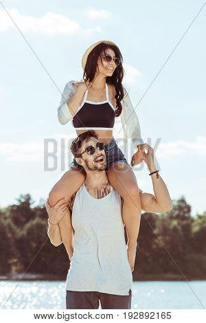 Handsome Young Man Carrying Beautiful Girl On Shoulders At Beach