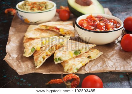 Mexican quesadillas, cheese and vegetables filled tortilla wraps with salsa and guacamole