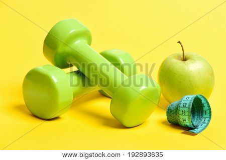 Apple In Greenish Yellow Color Near Dumbbells And Measuring Tape