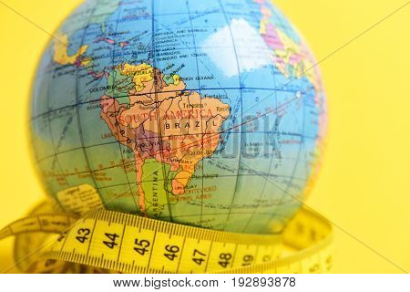 Globe and yellow measure tape isolated on bright yellow background. Concept of worldwide population migration and long distant travel close up