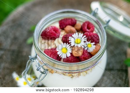 Full jar of muesli, yogurt, raspberries, nuts on a wood in a garden. Homemade breakfast cereals food. Healthy eating.