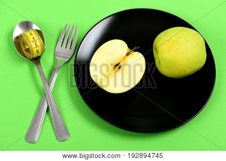 Plate In Black Color With Whole Apple Fruit And Half