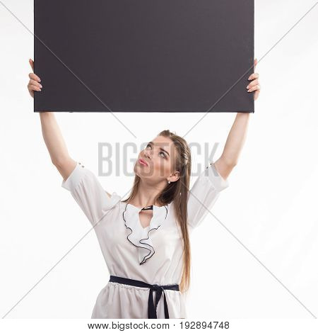 Young surprised woman portrait of a confident businesswoman showing presentation, pointing placard black background. Ideal for banners, registration forms, presentation, landings, presenting concept..