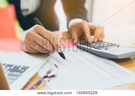 Close up Business man using calculator and laptop computer for calculating with finance paper tax accounting Accountant concept.