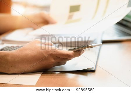 Business man do turnover graph chart of company and holding smart phone on wooden desk in office