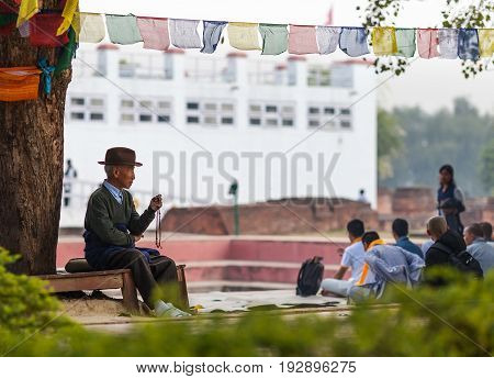 The elderly pilgrim reads mantras touching beads sitting under a tree against the background of the temple of the Maya Devi the mother of Buddha in the birthplace his holiness. On March 2 2017 Nepal Lumbini.