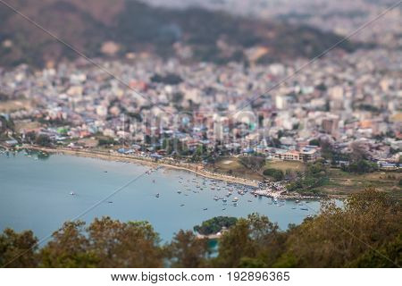 Panoramic view of pier and the boats with tourists on the lake Pheva and a part of the beautiful city of Pokhara. The photo is executed in toy style with use of technical properties of a lens tilt-shift from the observation deck at the World Pagoda.