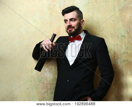 Man smiling and holding with bottle of wine in suit with red bow on background of beige color wall. Concept of party time and rest