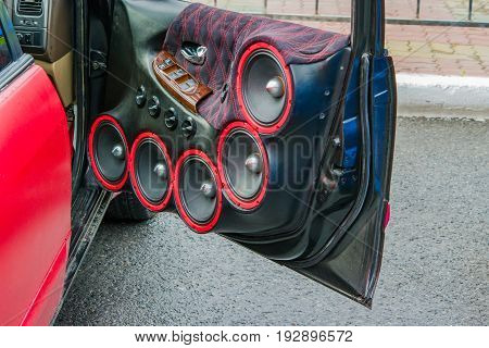 The door of the old retro red car with cloth upholstery and speakers