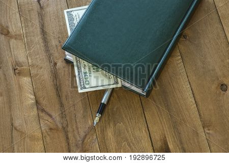 On the wooden surface is a diary with a pen and a part of the money bill is visible