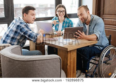 Creative thinker. Passionate devoted lively guy meeting with his friend in a cafe for working on their project and discussing business strategies
