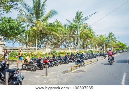 BALI- INDONESIA MARCH 08. 2017: Unidentified motorcyclist rides down the street. Legian's area. Legian is a suburban and beach area on the west coast of Bali.