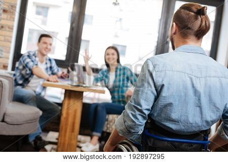 Great you joined us. Stylish easy going open man meeting his friends in a cafe while they waiting for him at the table and greeting him