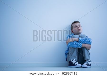 Lonely autistic child sitting on a floor in a room