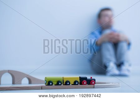 Toy train in a room and sad boy sitting on the floor