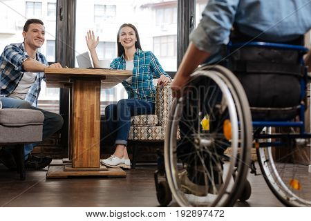 Nice seeing you. Awesome lively handicapped man meeting his colleagues in the cafe who working on their business project and asking him joining