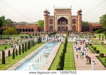 Agra India - April 30 2017 : People walking to Taj Mahal's western gate at sunrise Agra India