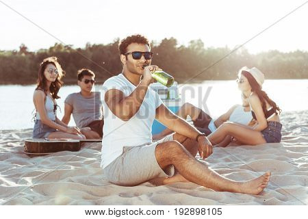 Young African American Man In Sunglasses Drinking Beer While His Friends Resting Behind On Sandy Bea