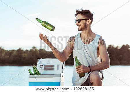Young Casual Man Smiling While Juggling Bottles Of Beer On Riverside