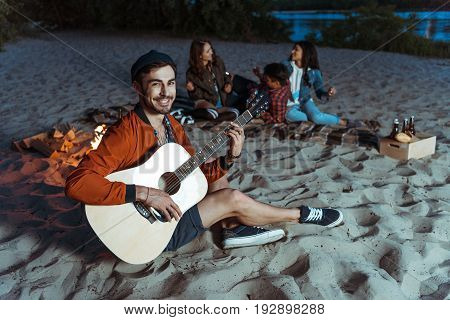 young smiling musician playing guitar while his friends sitting behind on sandy beach