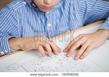 Focused little boy solving a white puzzle