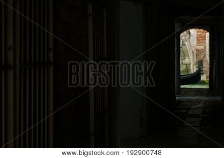 View of a typical gondola from a narrow and dark alley in Venice Veneto Italy Europe