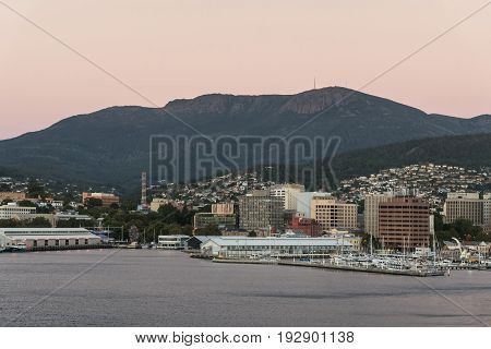 Hobart Australia - March 19. 2017: Tasmania. Pinkish sky over the forested mountain the backdrop of downtown. The bay and the high-rises near the coastline. Houses on the hill slopes.