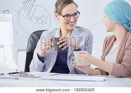 Young cancer patient and her oncologist drinking tea