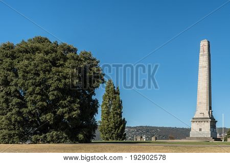 Hobart Australia - March 19. 2017: Tasmania. Tall white stone Cenotaph war memorial and trees on green hill with trees under blue sky.