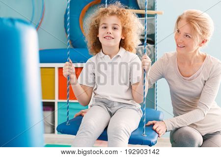 Boy sitting on a swing during therapy with a professional