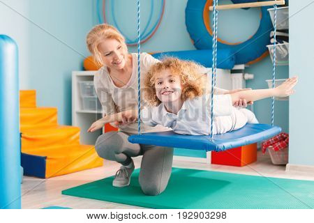 Woman helping a smiling boy to exercise on a therapy swing