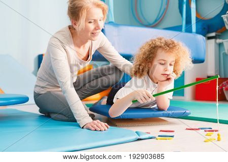 Focused kid having sensory integration session with professional therapist