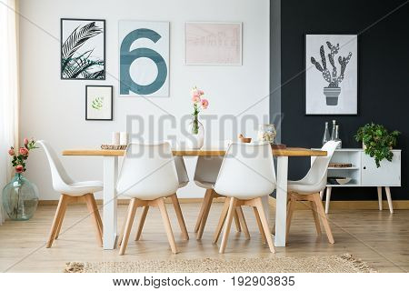 Wooden table with flowers in spacious bright room