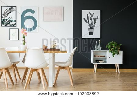 Black and white wall in dining room with plants