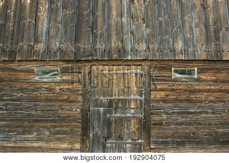 Old wooden barn building with door and windows. Rustic wood background