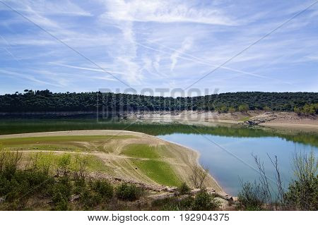 Embalse de Ricobayo with Reflection of Green Trees against Cloudy Sky in Sunny Day Outdoors. Zamora Castilla and Leon Spain