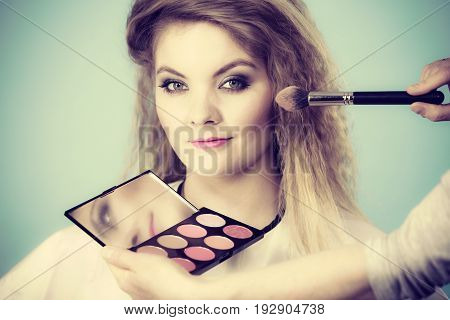 Makeup Artist Applying With Brush Rouge On Female Check