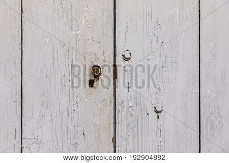 Cracked painted light grey white old textured wooden door with key hole background