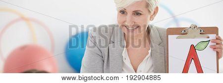 Female elegant speech therapist at work in the kindergarten