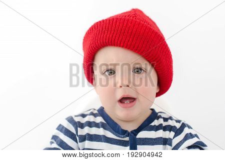 Kid in a red hat is indignant with two first teeth Baby with two milk teeth smiling at the camera , studio