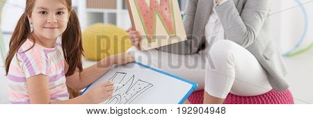 Girl learning letters with school counsellor on additional classes