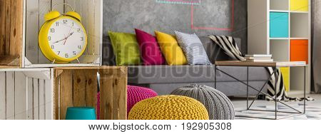 Creative living room with sofa poufs and alarm clock