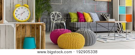 Modern studio apartment with sofa and three poufs