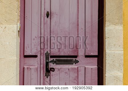 Red shabby french style door at southern France town with key hole and mail box slit