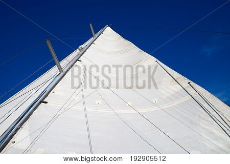 image of white sail against the blue sky