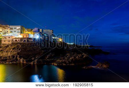 Dark night landscape of Puerto de Santiago and Atlantic ocean rocky shores. Tenerife island, Spain.
