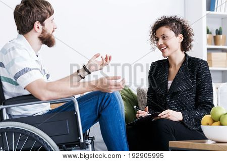 Young bearded man on wheelchair during home psychotherapy