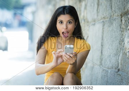 Shocked And Surprised Attractive Young Latin Woman Texting And Talking On Her Smart Cell Phone