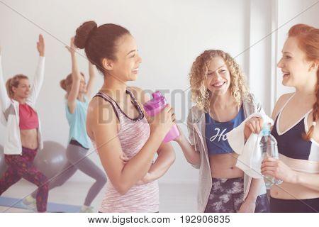 Female gym buddies taking five during workout