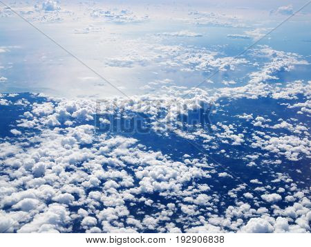 Mid-level cloudscape altocumulus white clouds. Altocumulus middle-altitude cloud in stratocumuliform. View from airplane white flying over sky.